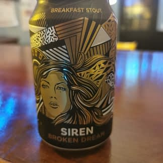 Dark can with a woman's face in gold & decorative lines and stripes surrounding it
