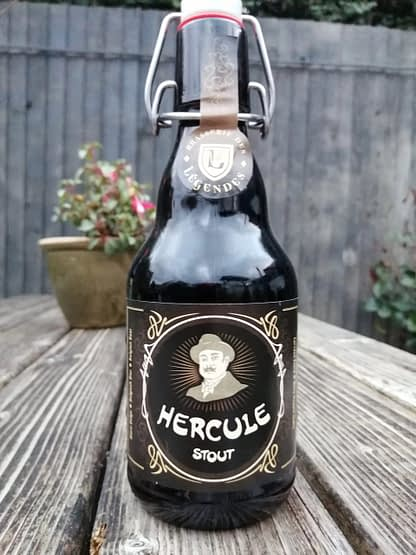 Dark brown flip top stubby bottle on the slat of a wooden picnic bench, label depicts Hercule Poirot.