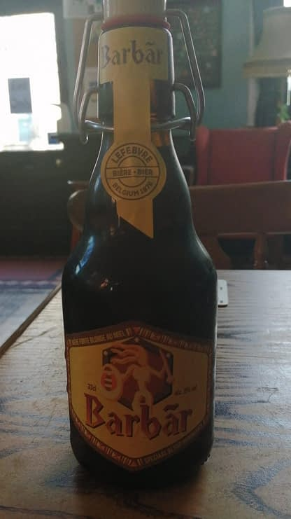 Dark brown stubby bottle with flip-top lid on a wooden table; yellow label depicts a stylised warrior with shield and spear