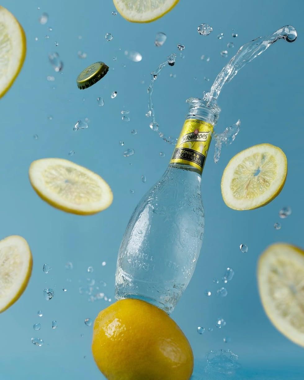opened soft drink bottle near flying lemon slices