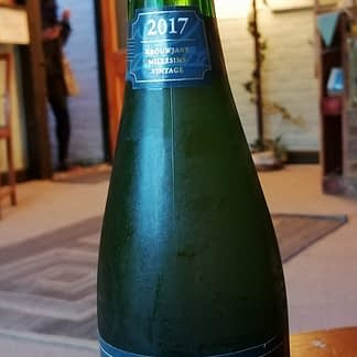 Green bottle with a caged cork top on top of a small stooll