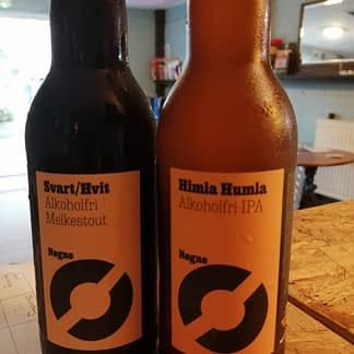 A pair of brown bottles side by side, one is filled with a darker liquid than the other both have orange labels