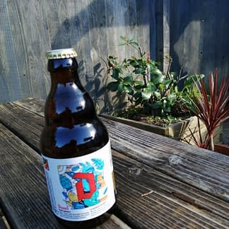 Stubby brown bottle on a picnic bench with a fence and plants in the background