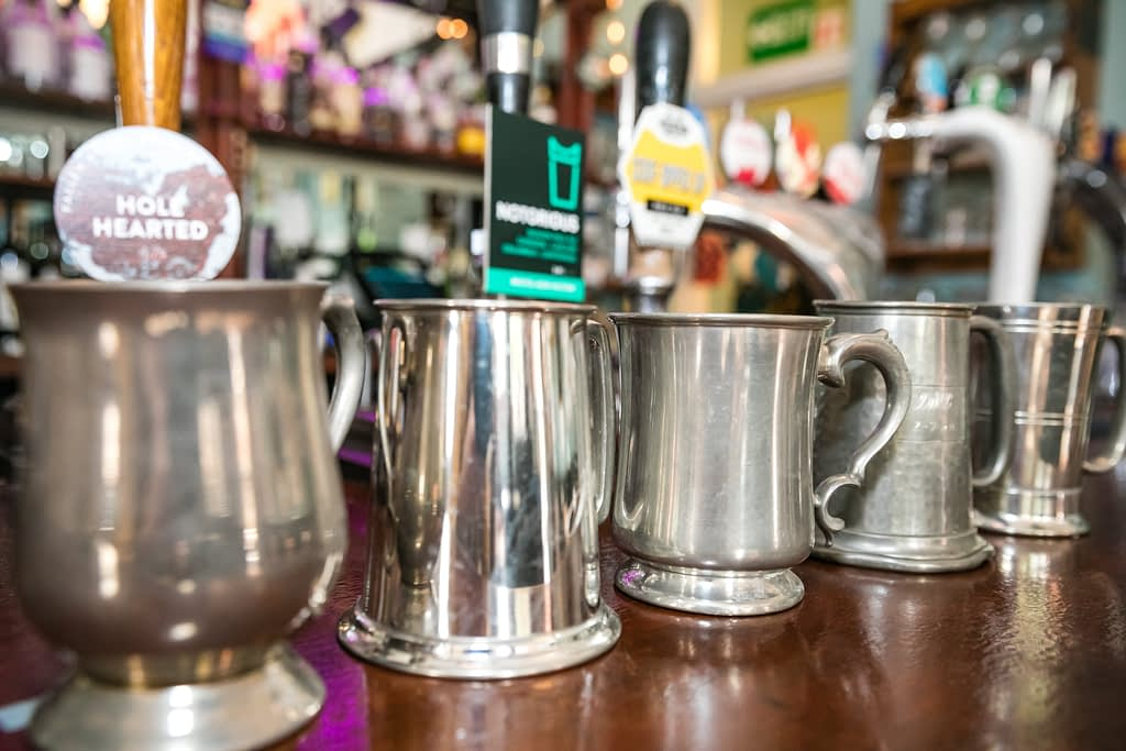 Five different shaped pewter tankards are arranged on a wooden bar top. They are getting further away from left to right of the image